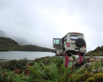 white vehicle parked near body of water surrounded by mountains under gray sky during daytime