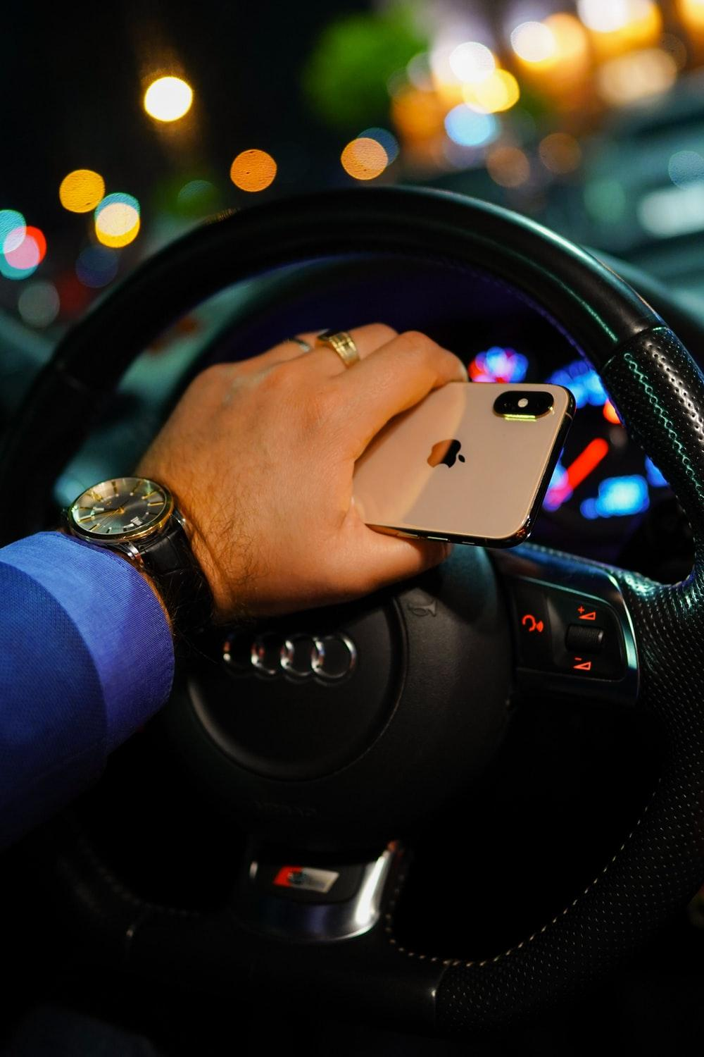 person holding gold iPhone Xs while driving black Audi vehicle